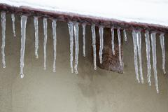 Icicles which are hanging down from a roof Stock Photos
