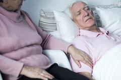 Woman supporting man with disease - stock photo