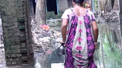 Woman wades to her house after a flood in Bengal, India Stock Footage