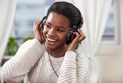 Cute young girl enjoying her music - stock photo
