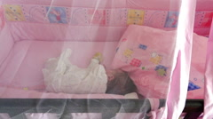 Ajar curtain on a cot, and a view of the sleeping baby Stock Footage