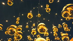 Golden Christmas balls on strings on the streets against the dark sky Stock Footage