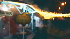 Christmas fair with a barbecue, glowing lights, blurred background - stock footage