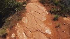 High Angle Viewpoint Of Hiker Walking Rocky Trail In Sedona AZ - stock footage