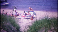 Family enjoys hidden spot on the beach - 3058 vintage film home movie Stock Footage