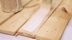 A footage of wooden boards being painted with white paint Stock Footage