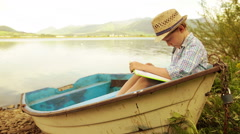 Little lad seats in the boat reading the book Stock Footage