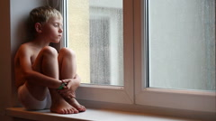 Lonely little boy waits for his parents to come home sitting on the windowsill Stock Footage