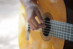 Female hand playing an acoustic guitar Stock Photos