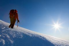 Stock Photo of Climber walks on a glacier. Winter season, clear sky.