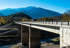 Bridge across the river in the French Pyrenees and picturesque mountain range Stock Photos