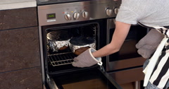 Baking, young girl taking cake out of the oven Stock Footage