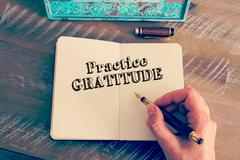 Motivational message PRACTICE GRATITUDE written on notebook - stock photo