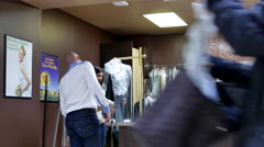 Man taking his pants at dry cleaning store  inside Coquitlam shopping mall Stock Footage