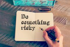 Motivational message DO SOMETHING RISKY written on notebook - stock photo