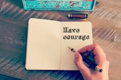 Motivational message HAVE COURAGE written on notebook Stock Photos