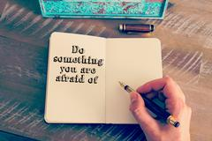 Motivational message DO SOMETHING YOU ARE AFRAID OF written on notebook Stock Photos