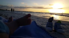 Low view of baby's foot. baby lying in the sand on beach watching sunset Stock Footage