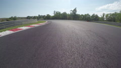LOW ANGLE VIEW: Race car competing and driving fast on race track lap Stock Footage