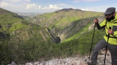 Hiker walking from right to left out of frame on a rocky terrain. Dolly shot Stock Footage