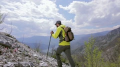 Hiker in nature. Diagonal movement on a rocky terrain with a view. Dolly shot Stock Footage