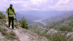 Male hiker walking towards the camera on a rocky terrain with a view. Dolly shot - stock footage