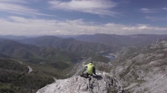 Male hiker enjoying a view with a lake. Dolly shot right to left, wide angle - stock footage