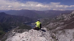 Male hiker enjoying a view with a lake. Dolly shot left to right Stock Footage