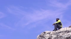 Male hiker sitting on a rock, enjoying the view. Stock Footage