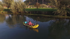 AERIAL: Couple kayaking on river, woman takes picture of pretty nature - stock footage