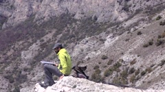 Hiker with a laptop on a rocky terrain with beautiful scenery - stock footage