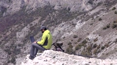 Stock Video Footage of Hiker with a laptop on a rocky terrain with beautiful scenery