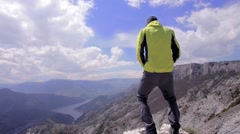 Man urinating in nature with beautiful scenery. Dolly shot Stock Footage