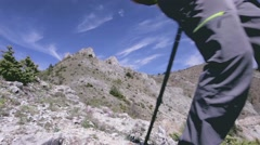Hiker descending rocky terrain towards the camera and out of frame. Dolly shot - stock footage
