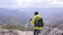 Male hiker stops to enjoy a view with a lake. Dolly shot Stock Footage