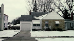 Sideways view of suburban houses on a snowy, tree-lined street in Illinois Stock Footage