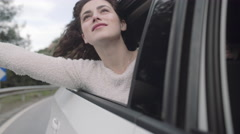 Young adult female hanging out of car window enjoying fresh air Stock Footage