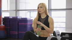 Stock Video Footage of athlete sexy woman drinks water with a towel and rub the face and neck, with