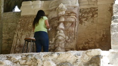 Unidentifiable female archeologist works on restoration of Maya face sculpture Stock Footage