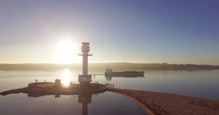 Aerial view of an beach in the morning sun with an lighthouse Stock Footage