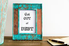 Vintage photo frame on wooden table with text GET OUT OF DEBT - stock photo