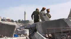 Mosque in background, Soldiers search for injured people Stock Footage