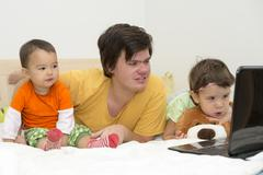 big brother watching cartoons with his younger sisters - stock photo