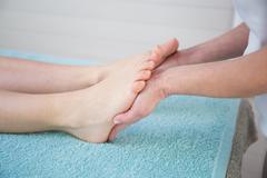 Osteopath doing reflexology massage on female foot against colorful backgroun - stock photo