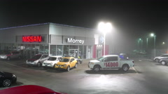 Nissan automobile dealership with fully smog at night Stock Footage