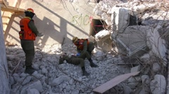 Paramedic administers infusion to injured soldier in the rubble  - stock footage
