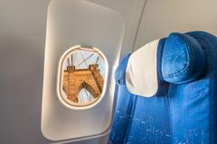 Airplane windo with view on Brooklyn Bridge, New York. Tourism concept Stock Photos