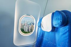 Airplane window with view on Hong Kong. Tourism and travel concept Stock Photos