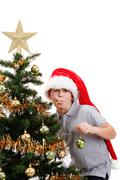 Boy with santa hat sticking out tongue at  the Christmas tree Stock Photos