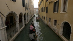 Paddling a gondola by a building with arches in Venice Stock Footage